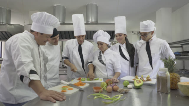 chef observing his student chop a tomato  in class - food and drink stock videos & royalty-free footage