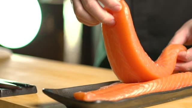 vídeos de stock, filmes e b-roll de chef escolhendo salmão cru na tábua de corte na cozinha do restaurante japonês - sashimi