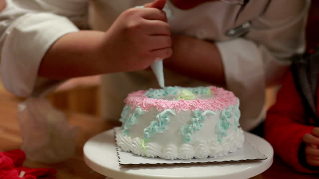 chef piping cream on birthday cake to make swirl decoration