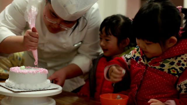 chef piping cream on birthday cake while baby girls eating candy