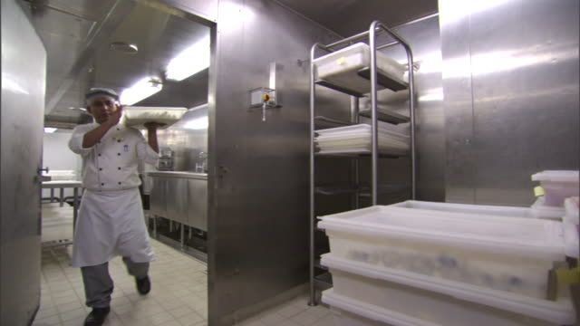 a chef places a bin of food into a walk-in refrigerator. - refrigerator stock videos & royalty-free footage