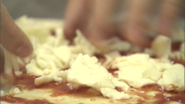 a chef places cheese and toppings onto a pizza. - tomatensoße stock-videos und b-roll-filmmaterial