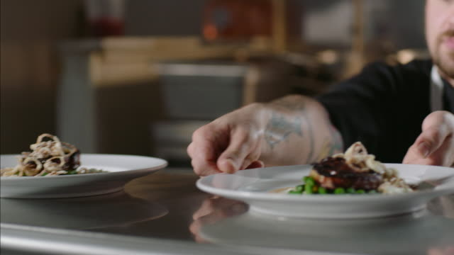 chef places finished entr_es on ready counter and waiter picks them up for table service in restaurant kitchen - lokal stock-videos und b-roll-filmmaterial