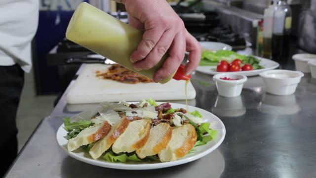 vidéos et rushes de chef met la touche finale sur repas - salade verte