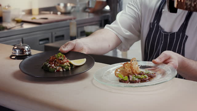 chef placing two main courses on counter for waiter to serve - gourmet stock videos & royalty-free footage