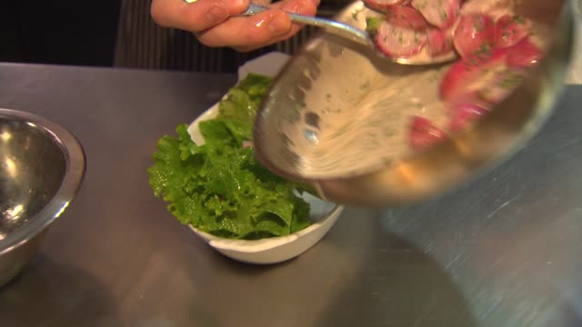 chef plates braised radishes on bed of lettuce at chicago restaurant next bistro on january 31 2015 in chicago illinois - braised stock videos and b-roll footage