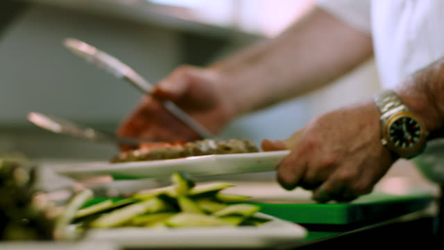 a chef plates some freshly cooked lamb skewers in a restaurant - mediterranean culture stock videos & royalty-free footage