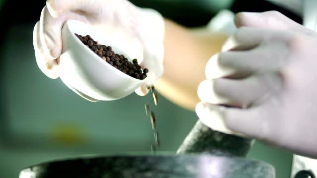 Chef pounding and grinding black pepper in a mortar.