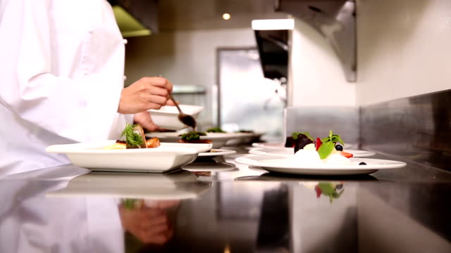 Chef pouring sauce over dishes