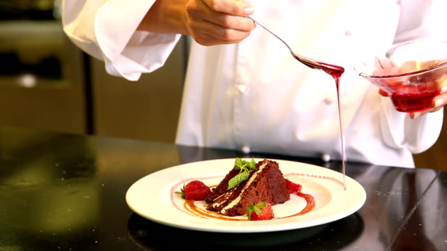 Chef pouring strawberry sauce over chocolate cake