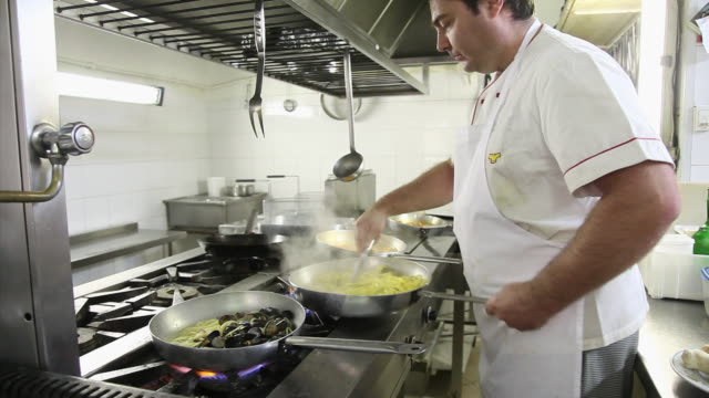 chef pours olive oil into pans containing pasta - chef stock videos & royalty-free footage