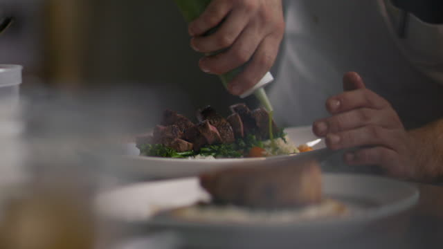 chef pours special sauce around dinner plate in restaurant kitchen - gourmet küche stock-videos und b-roll-filmmaterial