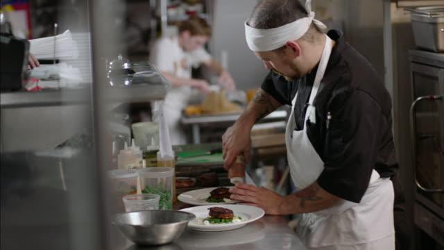 Chef pours special sauce around dinner plates in restaurant kitchen
