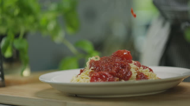 chef pours tomato sauce over fresh pasta - man and machine stock videos & royalty-free footage