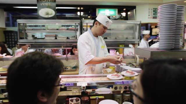 WS A chef prepares sushi in a sushi-go-round restaurant / Tokyo, Japan