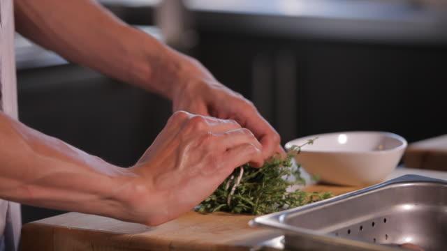 Chef prepares thyme bouquet in restaurant