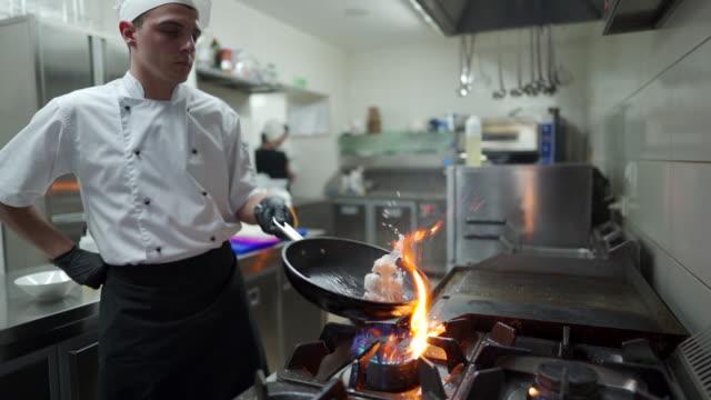 vídeos y material grabado en eventos de stock de chef preparando una comida en sartén en la cocina - chef