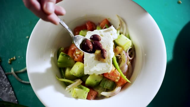 chef preparing a traditional greek salad - cucina mediterranea video stock e b–roll