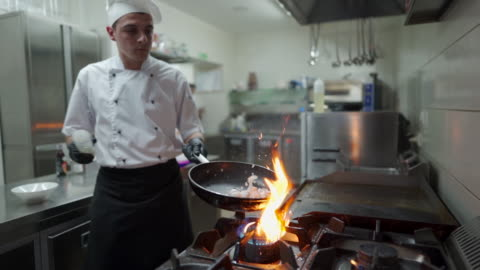 vídeos y material grabado en eventos de stock de chef preparando comida flambe en una sartén en un quemador de estufa de gas en la cocina comercial - sartén plana