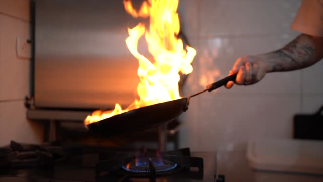 chef preparing flame meal using pan in a commercial kitchen - commercial kitchen stock videos & royalty-free footage