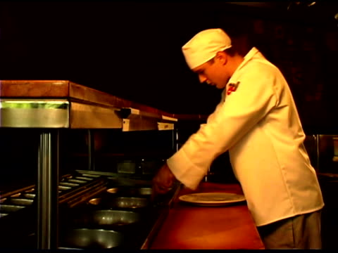 chef preparing food in restaurant kitchen - dreiviertelansicht stock-videos und b-roll-filmmaterial