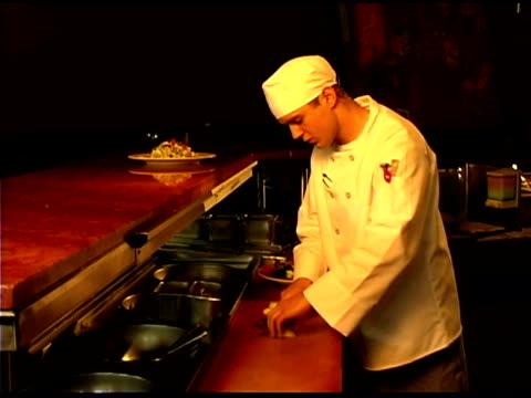 vídeos y material grabado en eventos de stock de chef preparing food in restaurant kitchen - encuadre de tres cuartos