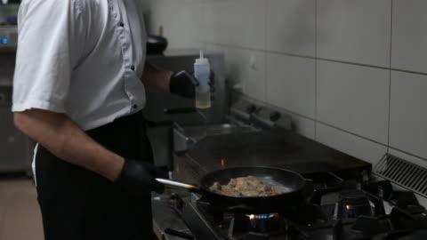 vídeos y material grabado en eventos de stock de chef preparando comida en cocina comercial - sartén plana