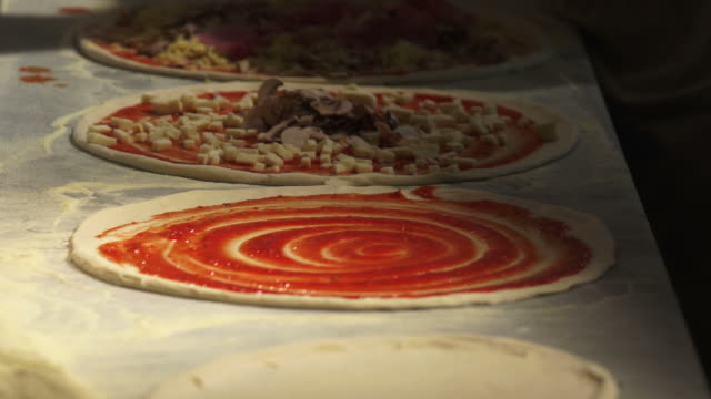 vídeos de stock e filmes b-roll de chef preparar pizzas close-up - geschwindigkeit
