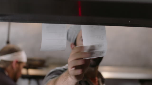 vídeos de stock e filmes b-roll de chef pulls finished order ticket from counter and spikes it on check spindle in restaurant kitchen - encomendar