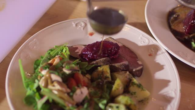 Chef puts cranberries and sauce on tenderloin roast