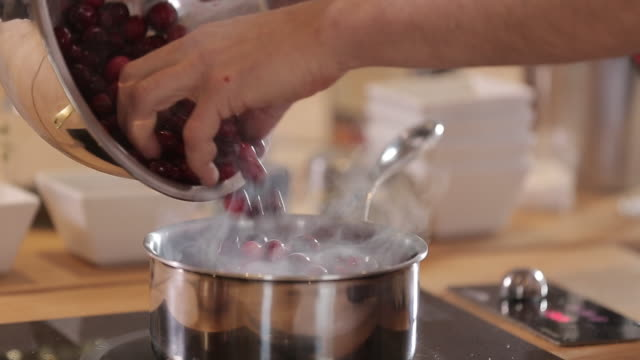 Chef puts cranberries in pot to make cranberry sauce