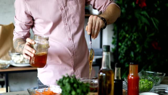 vidéos et rushes de chef mettant le miel dans le bol pour faire la sauce - société de consommation
