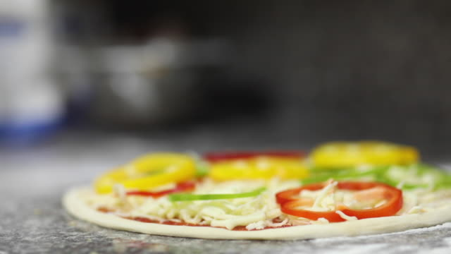 chef legt zutaten auf pizza vor dem backen - glove stock-videos und b-roll-filmmaterial