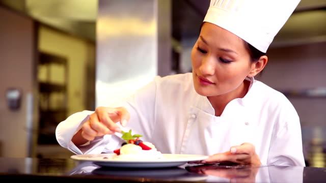 Chef putting mint leaf onto meringue