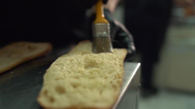シェフがパンに油を塗る - サンドイッチ作り点の映像素材/bロール