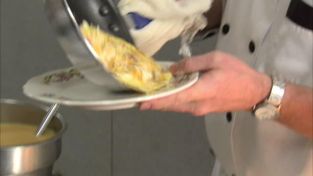 stockvideo's en b-roll-footage met cu tu chef putting omelet from pan onto plate / orem, utah, usa - orem utah