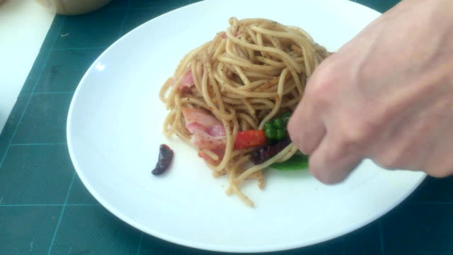 chef putting spaghetti onto plate