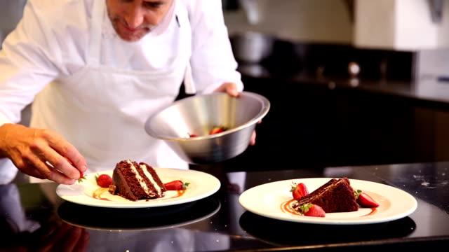 vídeos de stock, filmes e b-roll de chef colocar morangos na bolo de chocolate - comida doce