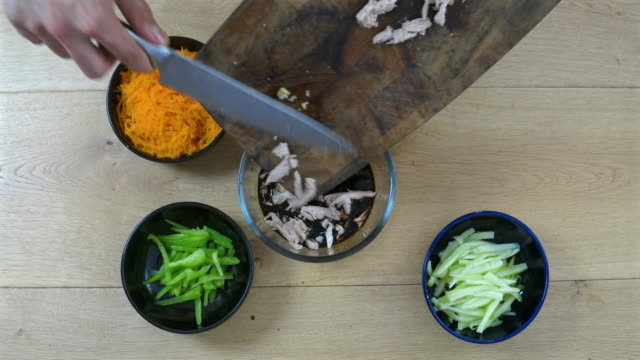 vídeos y material grabado en eventos de stock de chef putting strips of chicken from cutting board into a bowl, surrounded by freshly shredded cut vegetables, orange carrot, cucumber, green capsicum, - carrot top