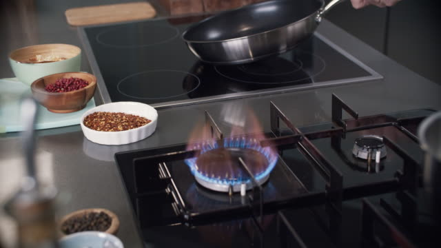 chef removes pan from stove top in professional kitchen - foodie stock videos and b-roll footage