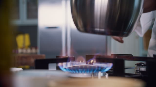 vídeos de stock, filmes e b-roll de chef removes pan from stove top in professional kitchen - formato bruto