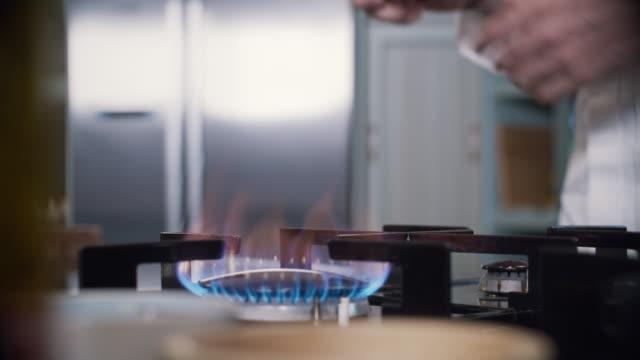 vídeos de stock e filmes b-roll de chef removes pan from stove top in professional kitchen - formato bruto