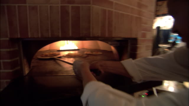 ms, chef removing pizza from pizza oven - pizza oven stock videos and b-roll footage