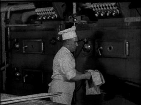 b/w 1930 chef removing rolls from oven in kitchen of ocean liner / educational - 1930 stock-videos und b-roll-filmmaterial