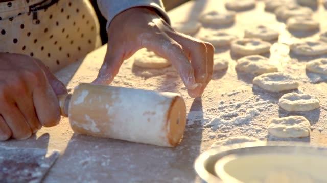 vídeos y material grabado en eventos de stock de chef rolling masas en un disco delgado antes de hacer palos de pan chinos. - al horno