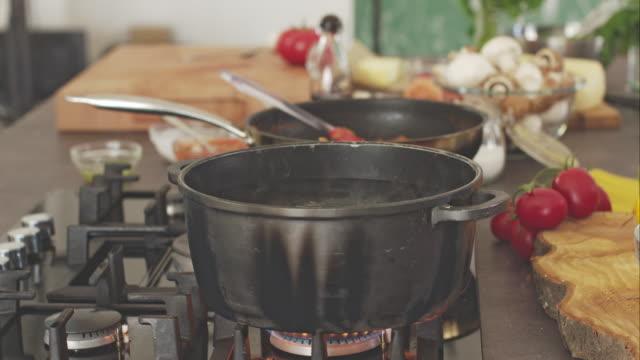 vídeos de stock, filmes e b-roll de salga chef água fervendo, adicionando massa - espaguete