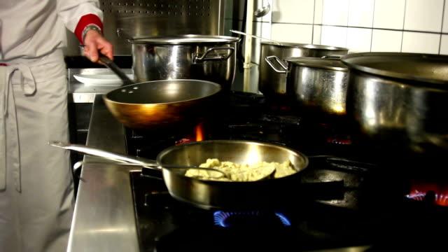 Chefkoch sauteeing Knoblauch in einer klassischen Küche