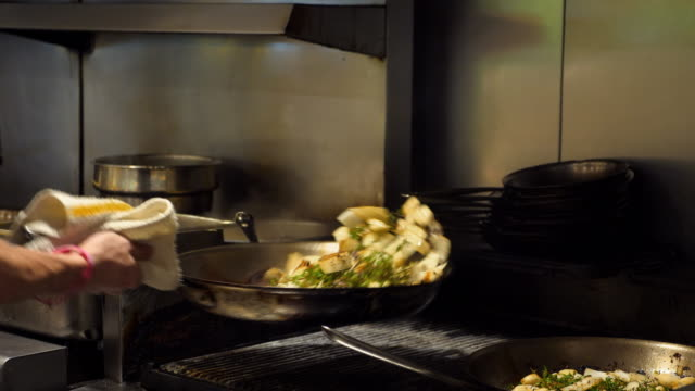 ms chef sauteing onions and herbs in preparation for evening meal service in restaurant kitchen - saute stock videos and b-roll footage