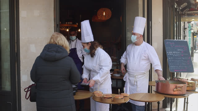 vidéos et rushes de chef sells lunch dishes to take away in front of his restaurant as cooks serving customers on the sidewalk on november 24, 2020 in paris, france.... - repas à emporter