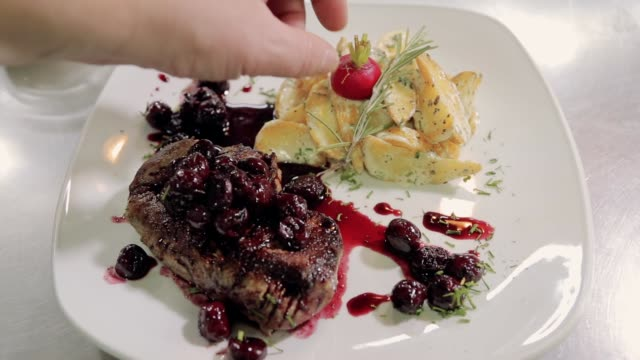 chef serving a dish of beef steak with cherries and potato as garnish - garnish stock videos & royalty-free footage
